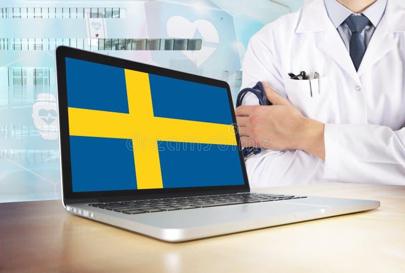 Sverige vårdsystem i techtema Svensk flagga på datorskärmen Doktor som står med stetoskopet i sjukhus royaltyfria bilder