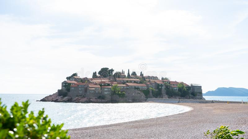 Sveti Stefan historical town island and paradise sand beach. Budva, Montenegro. Hotel in a small rock in the adriatic sea in a stock image
