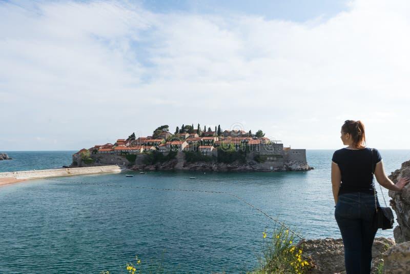 Sveti Stefan w Budva Montenegro młodej dziewczyny podróżniku Adriatycki morze z łodziami i stary miasteczko w wyspie Kamienny luk zdjęcia stock