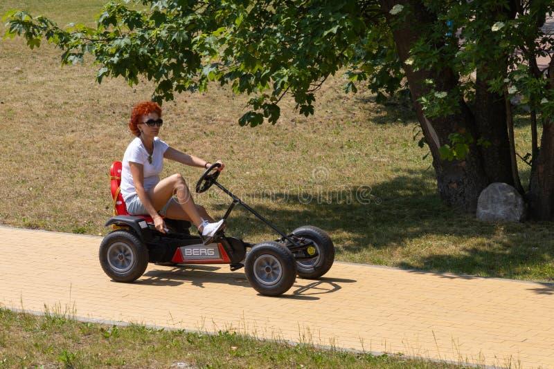 Svetlogorsk, Rusia - junio 8,2019: Mujer que conduce la bicicleta de tracción a las cuatro ruedas en parque de la ciudad foto de archivo