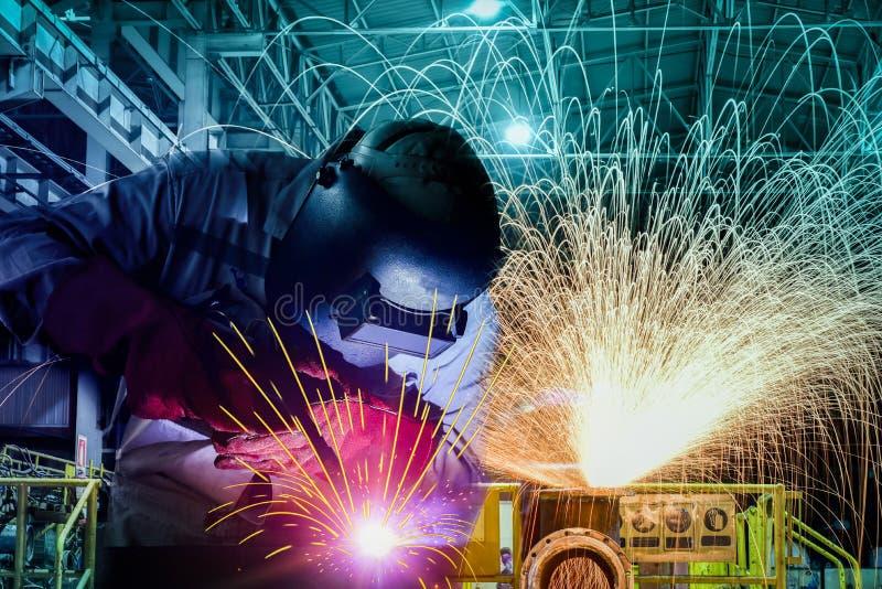 Svetsande procecc för industriarbetare vid bågen med gnistor som är ljusa i fabrik arkivbild
