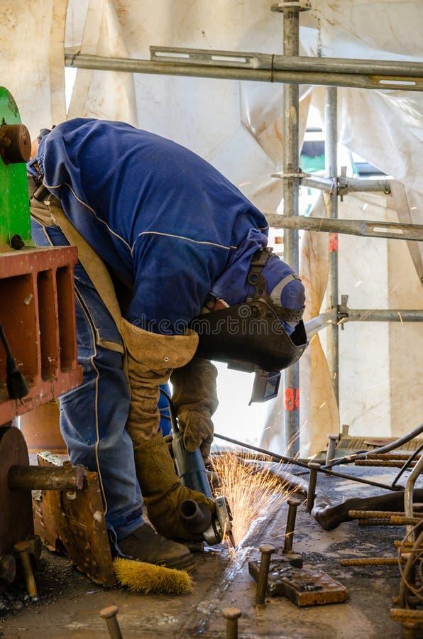 Svetsningarbetare med en radiell såg på en konstruktionsplats royaltyfri bild