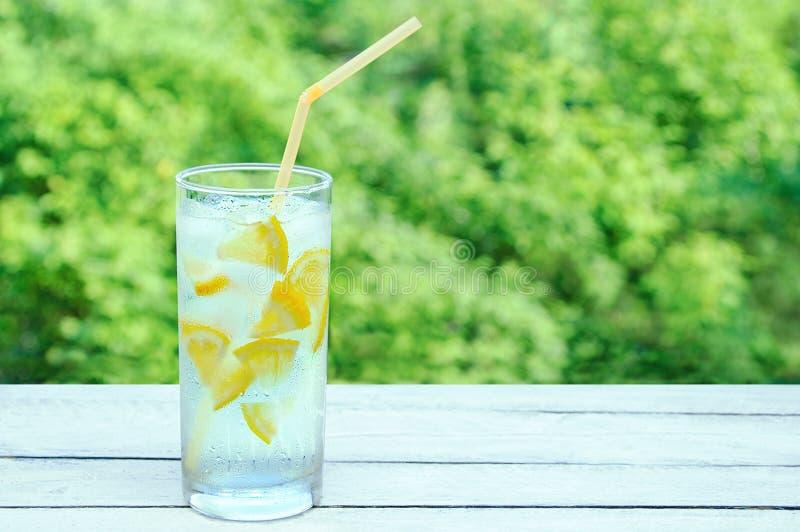 Svettigt exponeringsglas med en uppfriskande coctail med is och citronen På en träbakgrund fotografering för bildbyråer