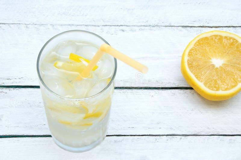 Svettigt exponeringsglas med en uppfriskande coctail med is och citronen På en träbakgrund arkivbilder
