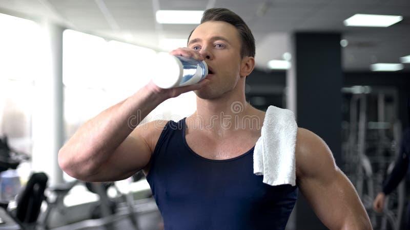 Svettigt idrottsmandricksvatten efter genomköraren, sund näring, aquajämvikt royaltyfri fotografi
