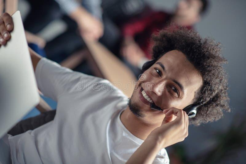 Sviluppatori di software afroamericani di risata dei pantaloni a vita bassa al computer all'ufficio di start-up immagine stock libera da diritti