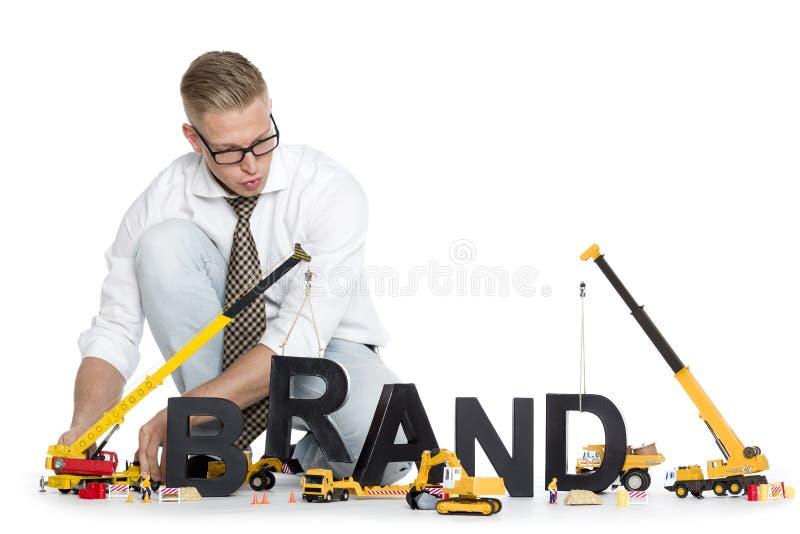La marca comincia su: Marca-parola della costruzione dell'uomo d'affari. fotografie stock libere da diritti