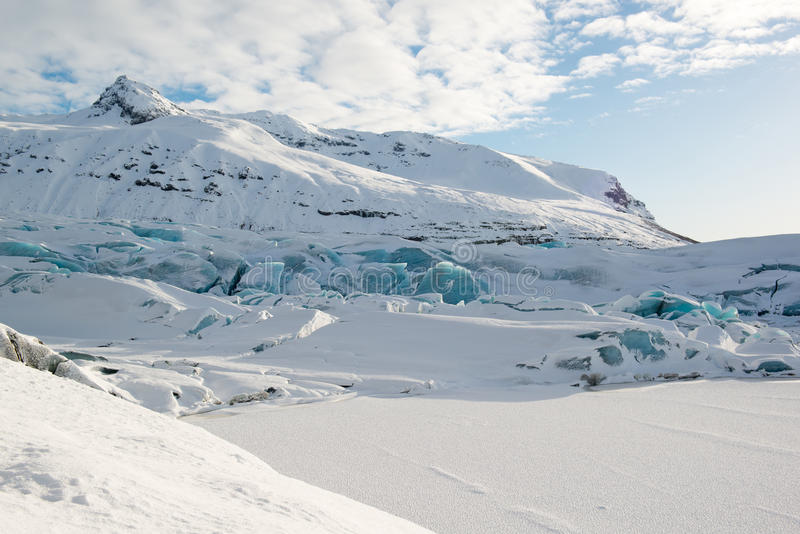 Svinafellsjokull冰川舌头在冬天,雪盖的蓝色冰山,冰岛 图库摄影
