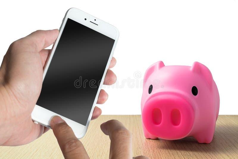 Svinbank med smartphonen och materielpengar fotografering för bildbyråer