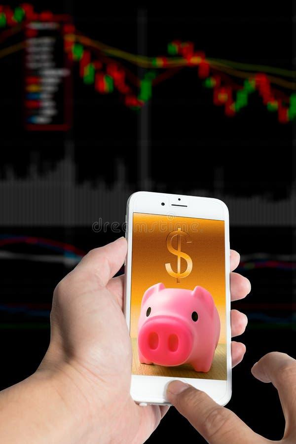 Svinbank med smartphonen och materielpengar arkivbilder