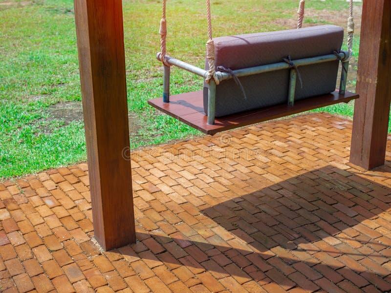 Svingbänk av trä med kudde på tegelgolv i trädgård royaltyfria foton