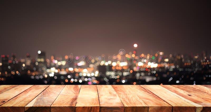 Svuoti del piano d'appoggio di legno bianco sulla città di notte della sfuocatura, paesaggio urbano fotografia stock libera da diritti