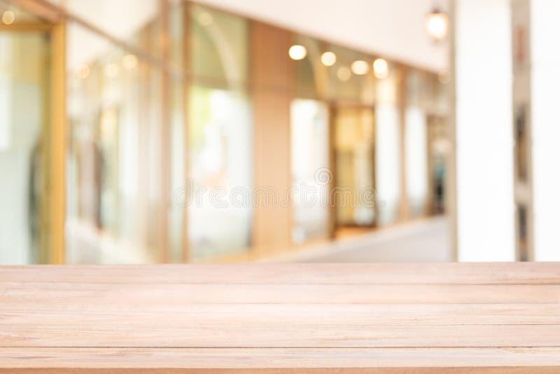 Svuoti della tavola di legno con sfuocatura il modo o il corridoio della passeggiata nella costruzione per comperare fotografia stock libera da diritti