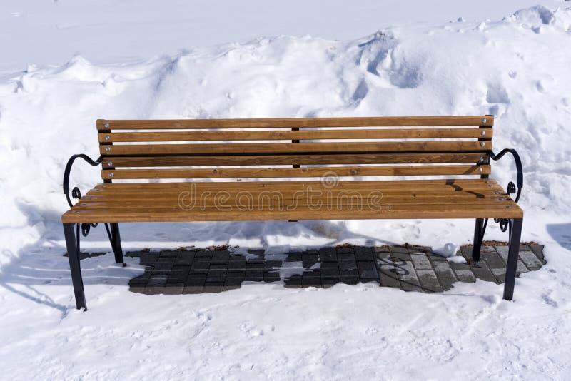 Svuoti il banco di legno coperto di neve nel parco dell'inverno fotografia stock