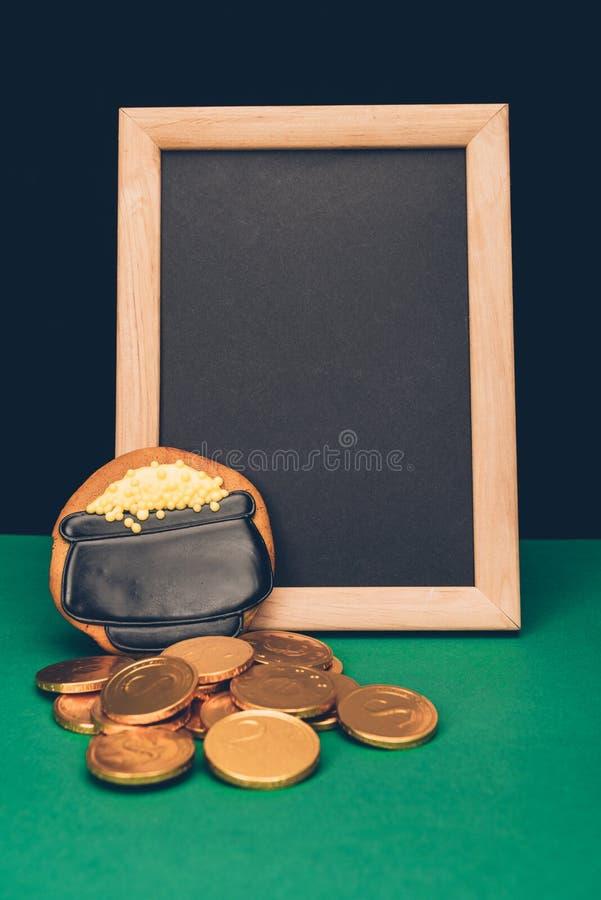 svuoti il bordo con le monete dorate ed il pan di zenzero sulla tavola verde, patricks della st fotografia stock