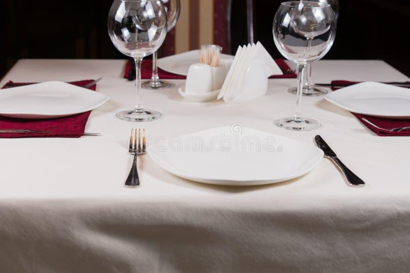 Svuoti il piatto bianco in una regolazione convenzionale della tavola fotografia stock