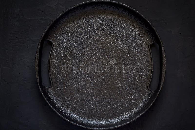 Svuoti il piatto rustico del ghisa su un fondo nero Spirito di vista superiore immagini stock libere da diritti