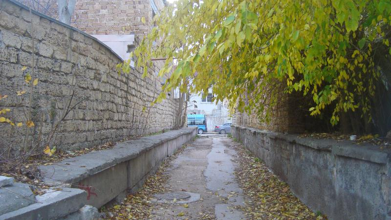 Svuoti il vicolo diritto e stretto fra i mura di mattoni nella vecchia città, un giorno nuvoloso fotografie stock