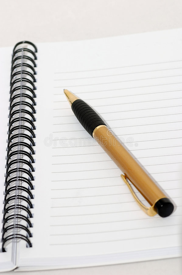 Svuoti l'anello in bianco, il blocchetto per appunti a spirale, una macro della penna dell'oro fotografia stock