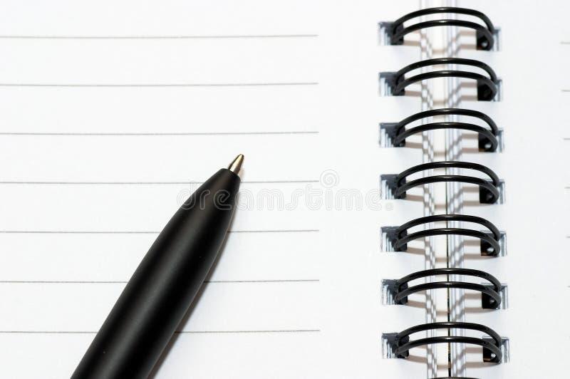 Svuoti l'anello in bianco, il blocchetto per appunti a spirale, una penna immagine stock libera da diritti