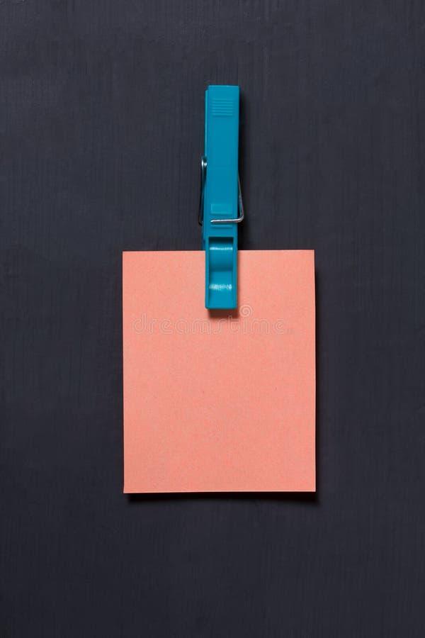 Svuoti l'autoadesivo rosa della carta del modello che appende con una molletta da bucato su buio immagine stock libera da diritti
