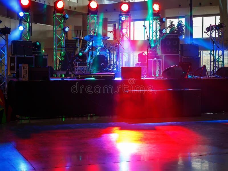 Svuoti la fase nella sala con le luci rosse, il fumo e l'attrezzatura di musica fotografia stock