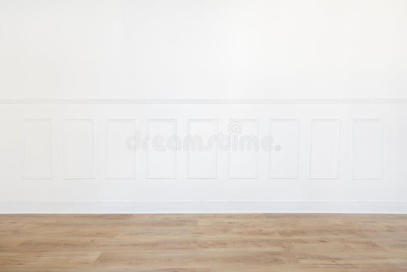 Svuoti la stanza bianca con il pavimento di legno e la parete sistemata legno immagine stock libera da diritti