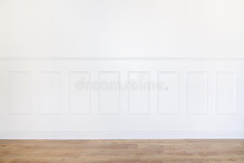 Svuoti la stanza bianca con il pavimento di parquet e la parete sistemata legno fotografie stock