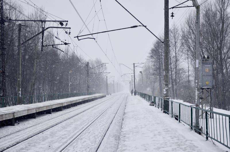 Svuoti la stazione ferroviaria in precipitazioni nevose pesanti con nebbia spessa Le rotaie ferroviarie vanno via in una nebbia b fotografia stock libera da diritti