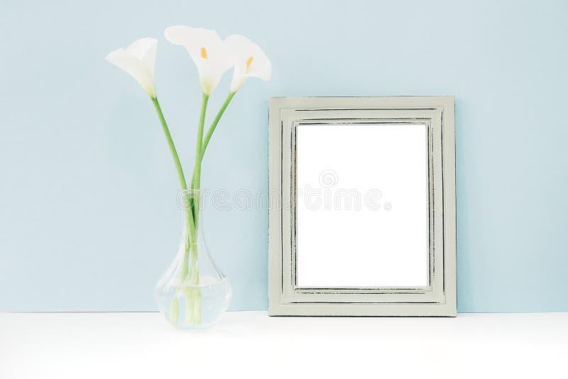 Svuoti la struttura di legno ed i fiori in vaso sulla tavola su fondo blu Derisione su fotografie stock