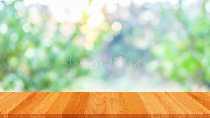 Svuoti la tavola di legno con il fondo di verde dell'estratto del bokeh fotografie stock