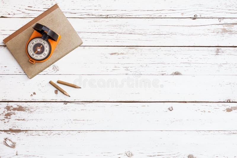 Svuoti la tavola di legno con il taccuino di lerciume del mestiere e la bussola nell'angolo, vista superiore immagini stock