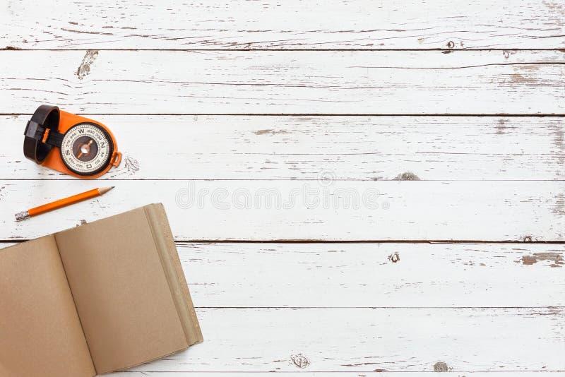 Svuoti la tavola di legno con il taccuino di lerciume del mestiere e la bussola nell'angolo, vista superiore fotografie stock
