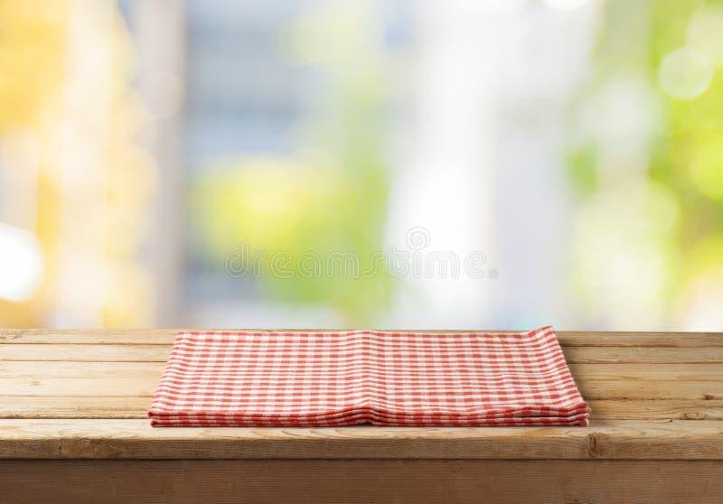 Svuoti la tavola di legno con la tovaglia sopra il backgroun astratto del bokeh immagini stock libere da diritti