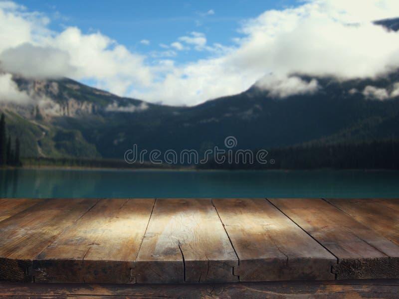 Svuoti la tavola di legno davanti al lago del celm ed alle montagne nevose fotografie stock