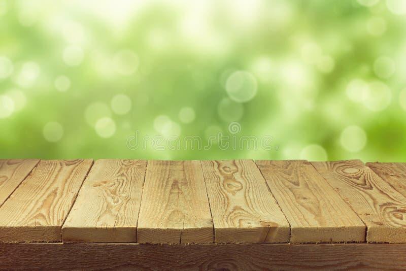 Svuoti la tavola di legno della piattaforma con il fondo del bokeh del fogliame Ready per il montaggio dell'esposizione del prodo fotografia stock