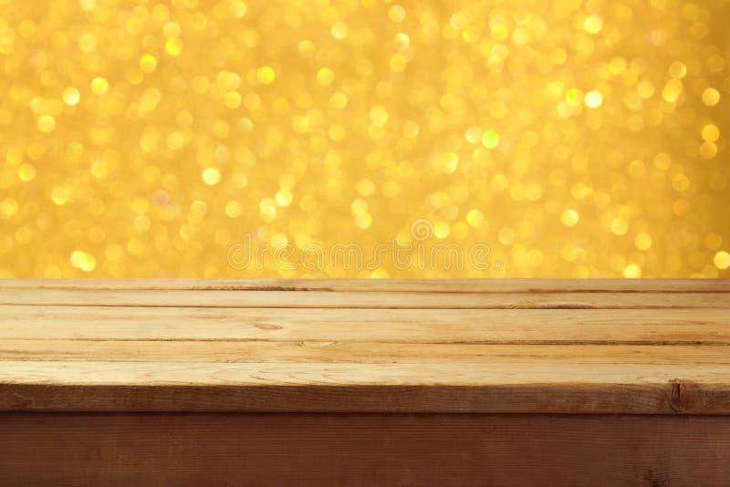 Svuoti la tavola di legno della piattaforma con il fondo dorato di festa del bokeh Ready per il montaggio dell'esposizione del pr immagine stock