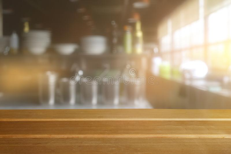 Svuoti la tavola di legno ed il fondo vago dell'interno della cucina fotografia stock