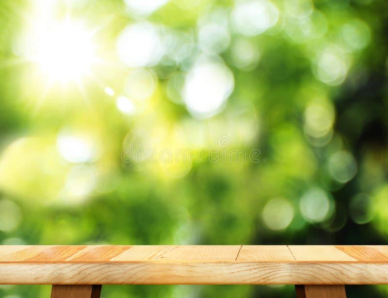 Svuoti la tavola di legno ed il fondo vago della luce del bokeh del giardino Mo immagini stock libere da diritti