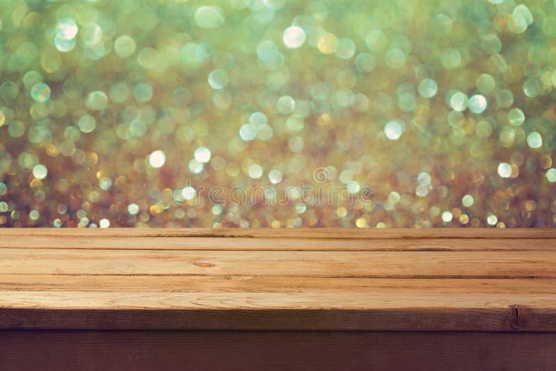 Svuoti la tavola di legno sopra il fondo festivo del bokeh di festa Scintillio dorato immagine stock