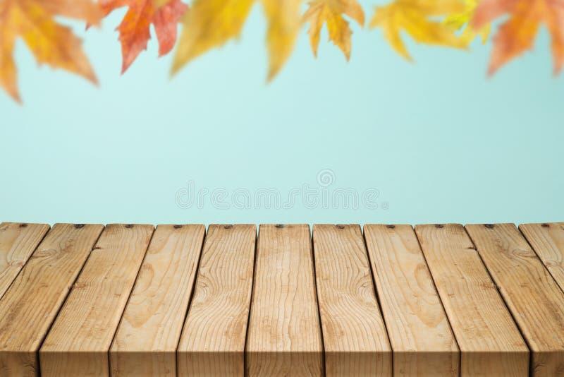 Svuoti la tavola di legno sopra il fondo vago delle foglie di autunno fotografie stock