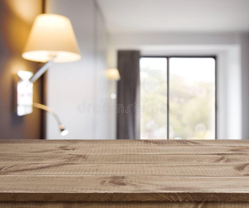 Svuoti la tavola di legno sul fondo semplice defocused dell'interno della camera di albergo fotografie stock libere da diritti
