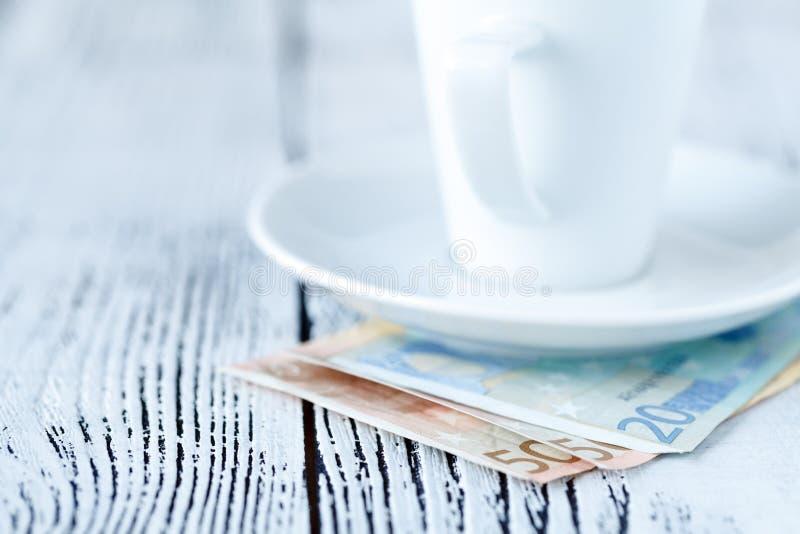 Svuoti la tazza di caffè macchiato finita e pagato in contanti da euro soldi sulla t fotografie stock libere da diritti
