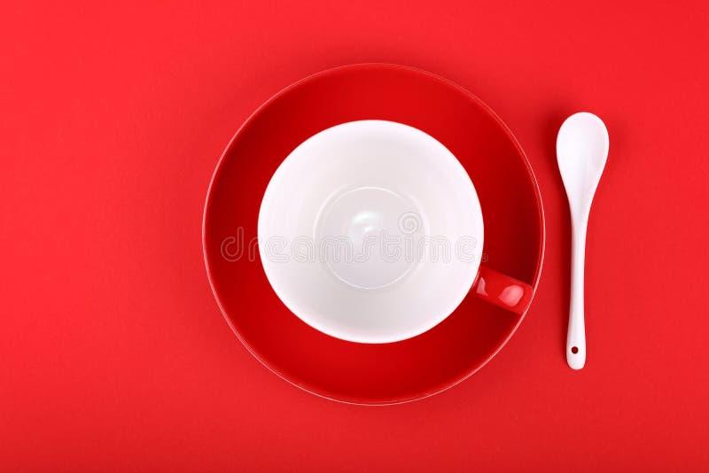 Svuoti la tazza ed il piattino di caffè bianchi del tè su rosso immagine stock libera da diritti