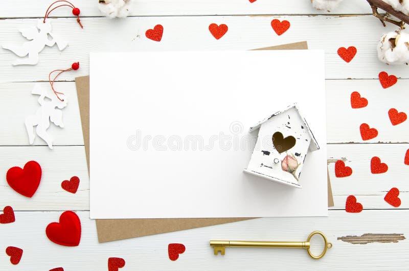 Svuoti le carte di carta decorate con cuore, casa miniatura con cuore, chiave dorata su fondo di legno, il giorno del ` s del big fotografia stock libera da diritti