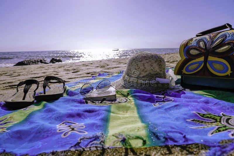 Swag auf dem Strand mit Pantoffelhutschutzbrillen und einer Tasche stockbilder