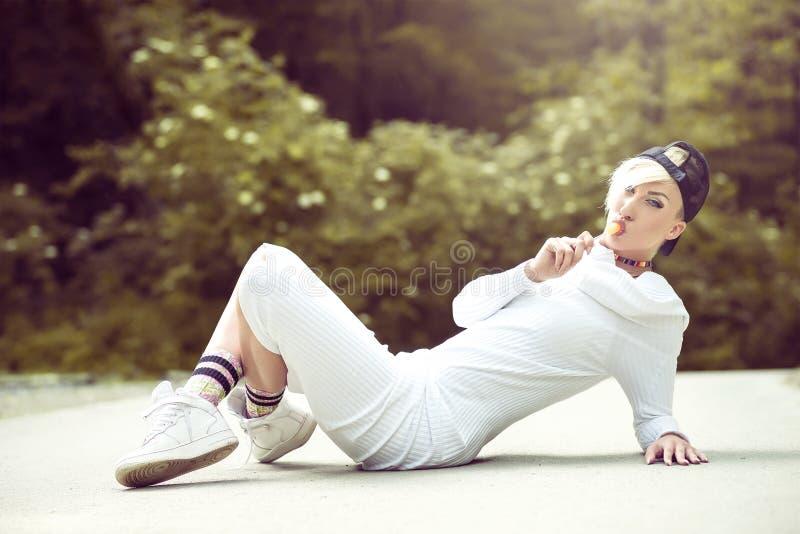 Swag het aantrekkelijke vrouwelijke meisje stellen met lolly in aard stock foto