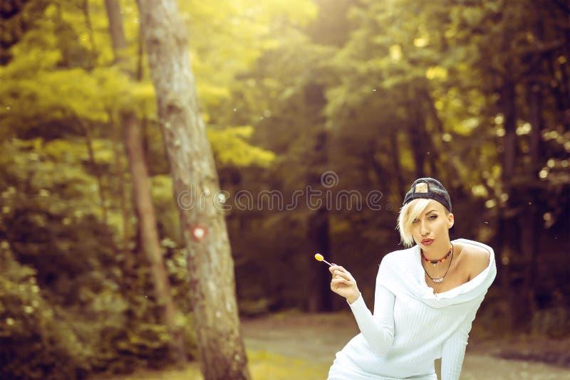 Swag het aantrekkelijke vrouwelijke meisje stellen met lolly in aard stock afbeeldingen