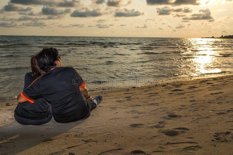 Swain som tillsammans sitter på stranden och den hållande ögonen på solnedgången, romans arkivbilder