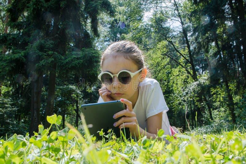 swallowtail för sommar för fjärilsdaggräs solig gullig flicka i solglasögon som ligger på grön gräsmatta med hennes grej vila för arkivfoto